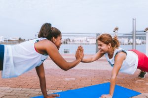 Two woman giving each other a high five while exercising